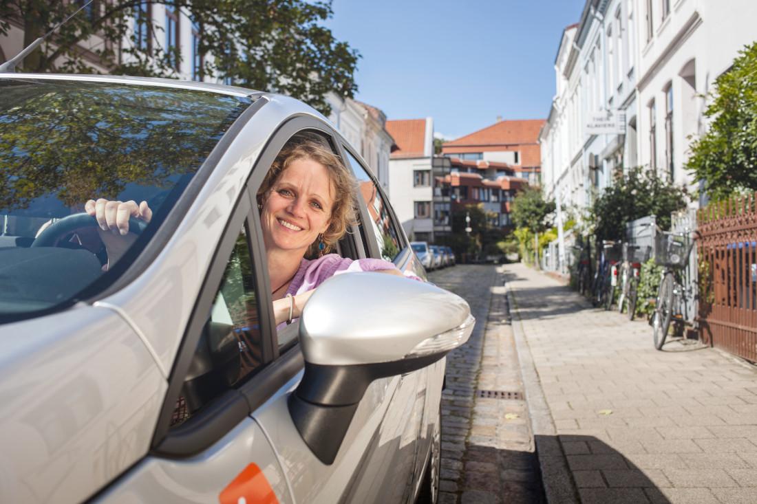 Eine Frau in einem rosa Pullover schaut lächelnd aus dem Seitenfenster eines silbernen Autos