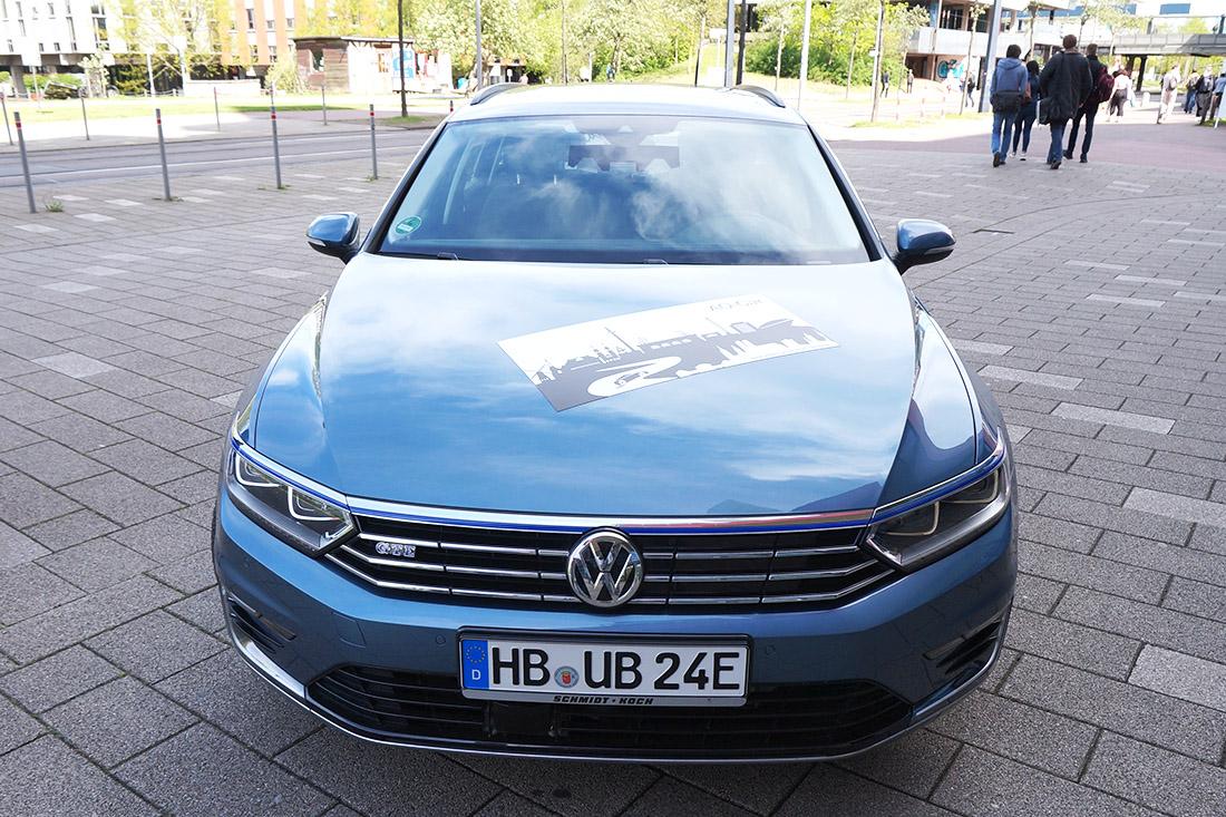 Ein hellblaues Auto der Marke VW direkt von vorn aufgenommen