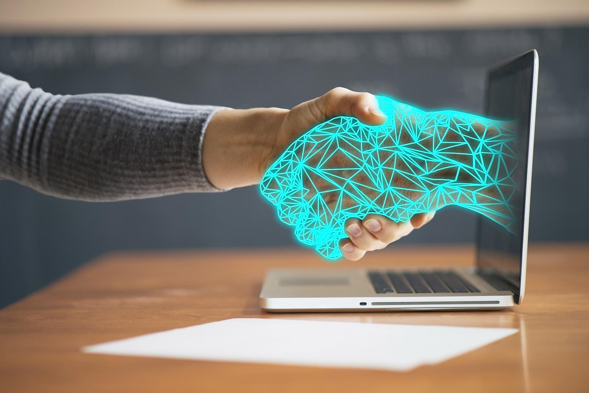 Eine digitale und eine menschliche Hand geben sich die Hand durch einen Laptop