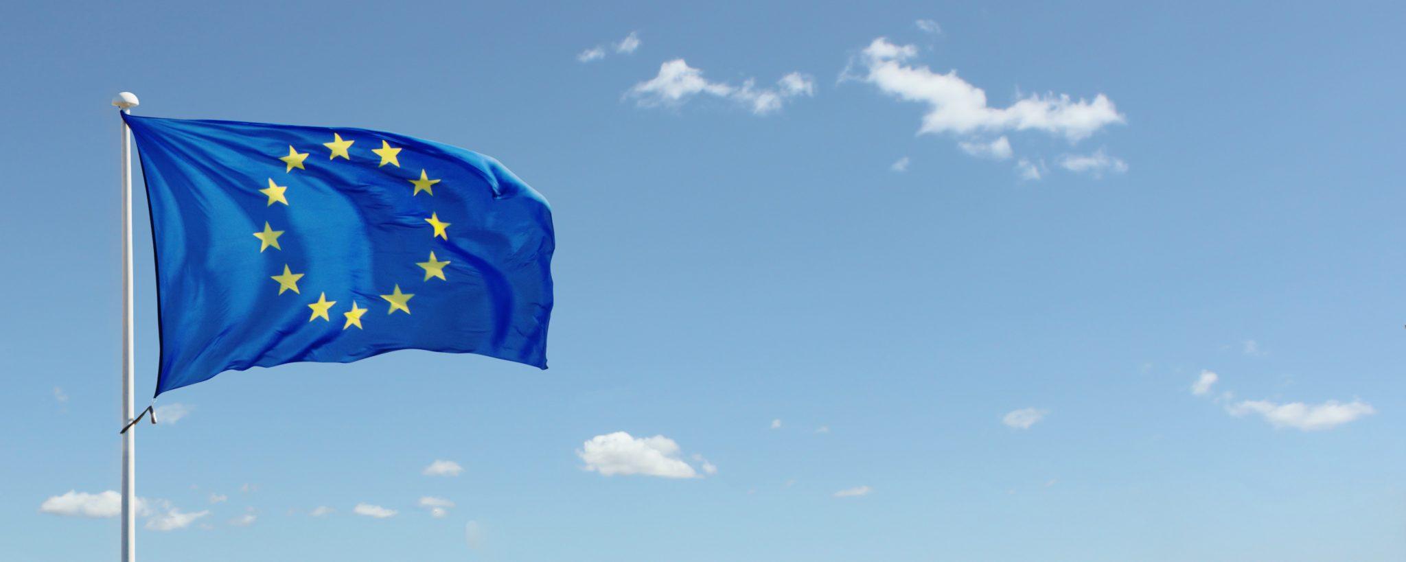 Eine Europaflagge vor leicht bewölktem Himmel.