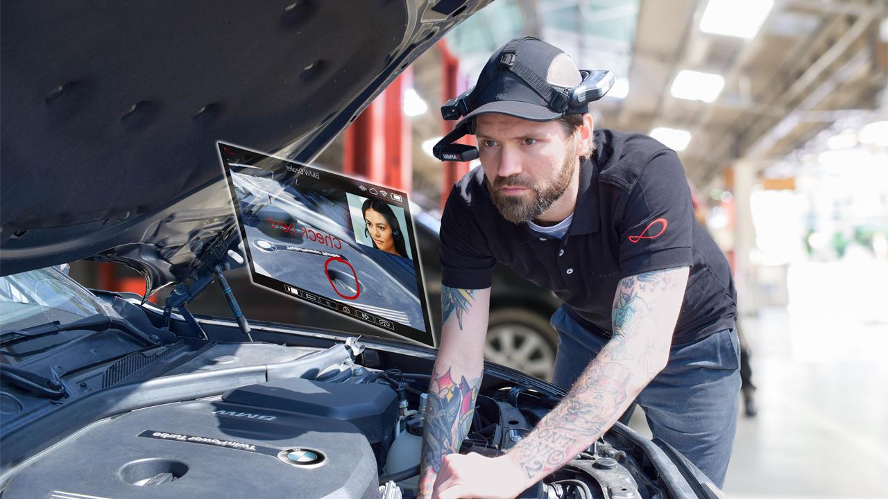 Ein Mann wartet ein Auto mit Hilfe einer Datenbrille