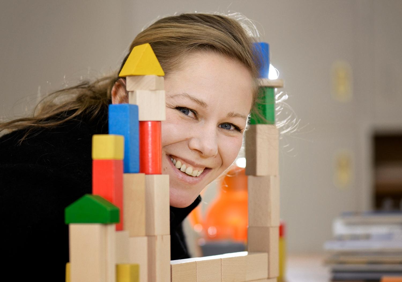 Ein Frau schaut durch zwei Baukastentürme