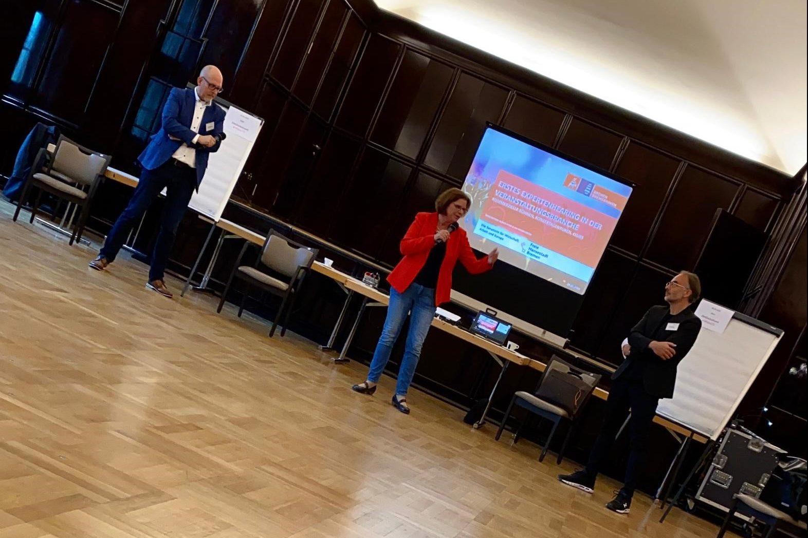 Drei Menschen bei einer Präsentation