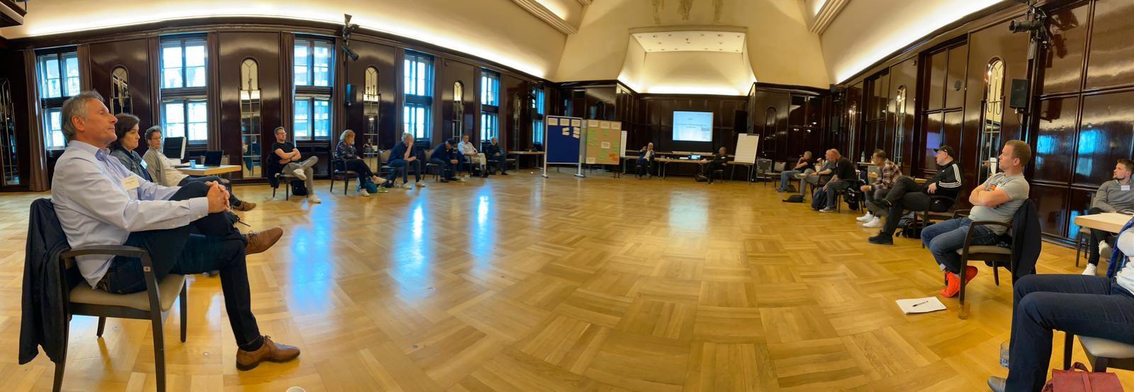 Menschen sitzen in einem großen Saal im Kreis