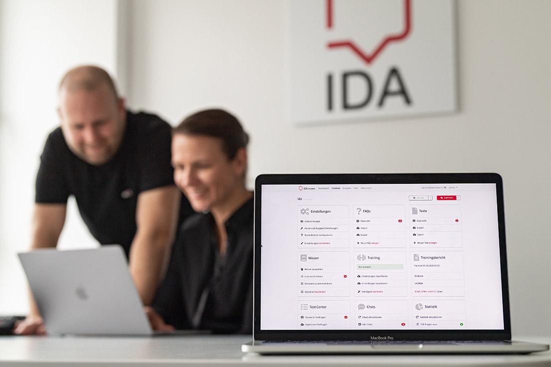 Ein Laptop auf einem Tisch, im Hintergrund das IDA Logo