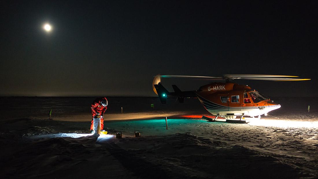 In der Dunkelheit prüft Spreen auf dem Eis wissenschaftliche Geräte, Bild: AW/Stefan Hendricks