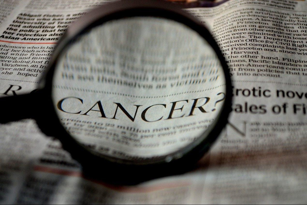 Eine Lupe liegt hochkant auf einer geöffneten Zeitung. Durch das Lupenglas ist vergrößert das Wort CANCER zu lesen.