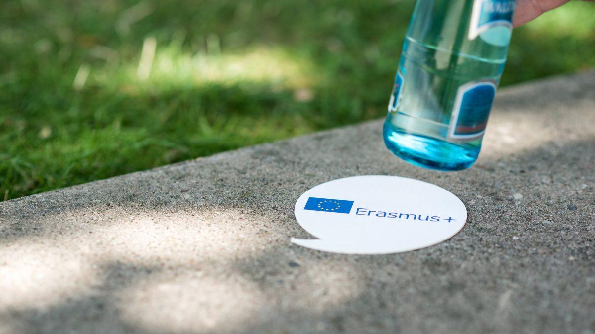 Ein Getränkeuntersetzer mit dem Erasmus + Logo, von dem eine Wasserflasche hochgehoben wird
