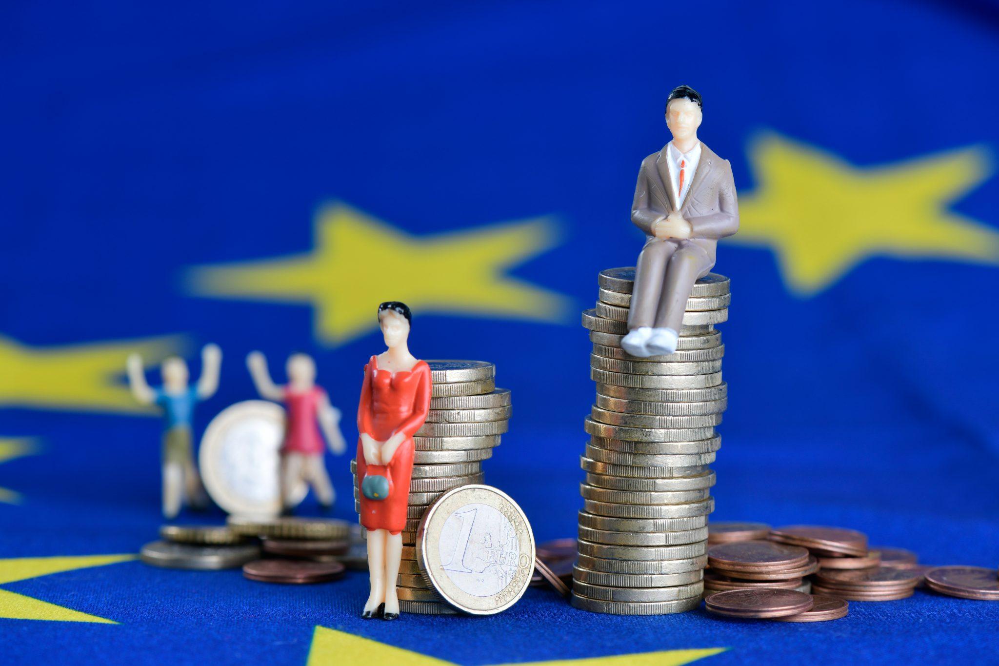 Spielzeugfiguren auf einer Europaflagge. Ein Mann sitzt auf einem hohen Stapel Euro-Münzen, eine Frau steht daneben mit einem nur halb so hohen Stapel Münzen.