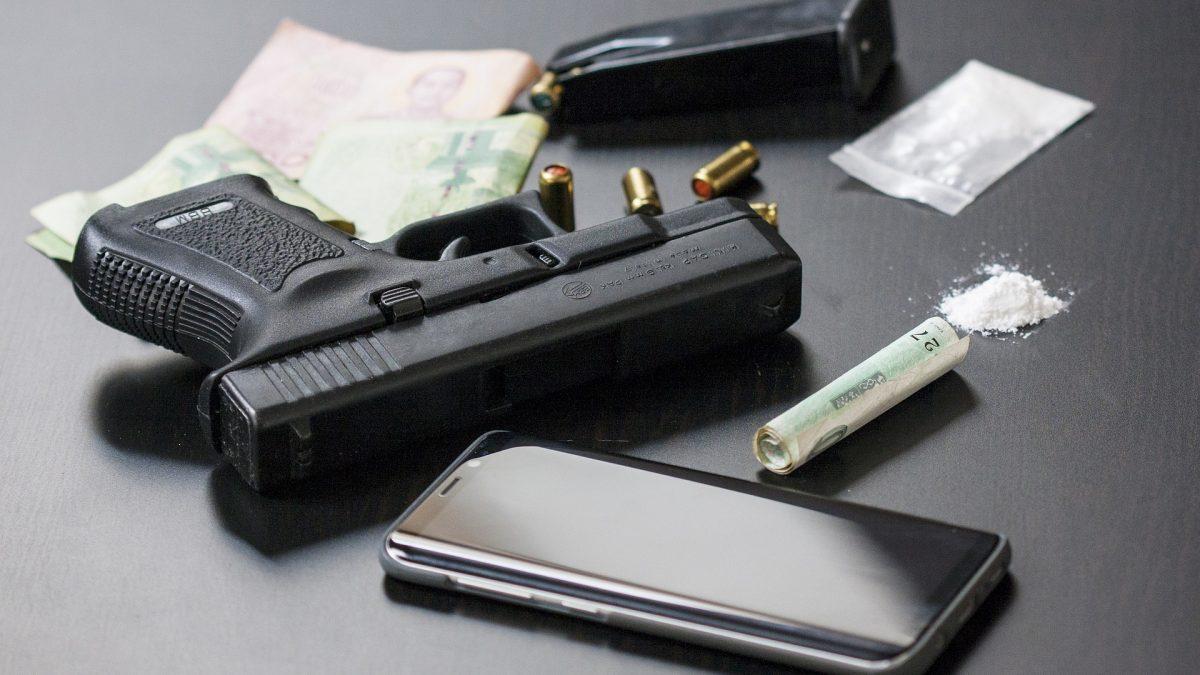 auf einer glatten schwarzen Oberfläche liegen eine Pistole, ein Smartphone und verschiedene Rauschgifte