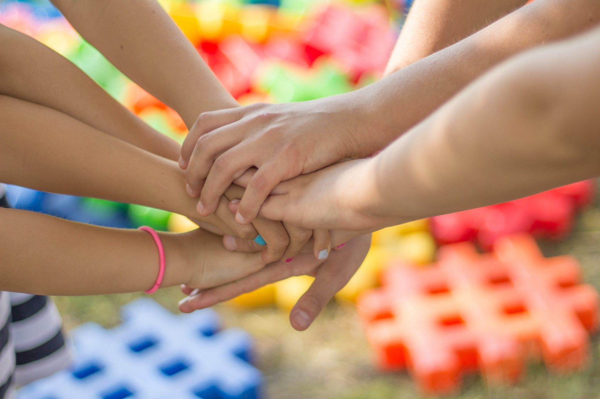 Hände von jungen Menschen, die im Kreis stehen (außerhalb des Bildes) und sich in der Mitte des Bildes an den Händen fassen