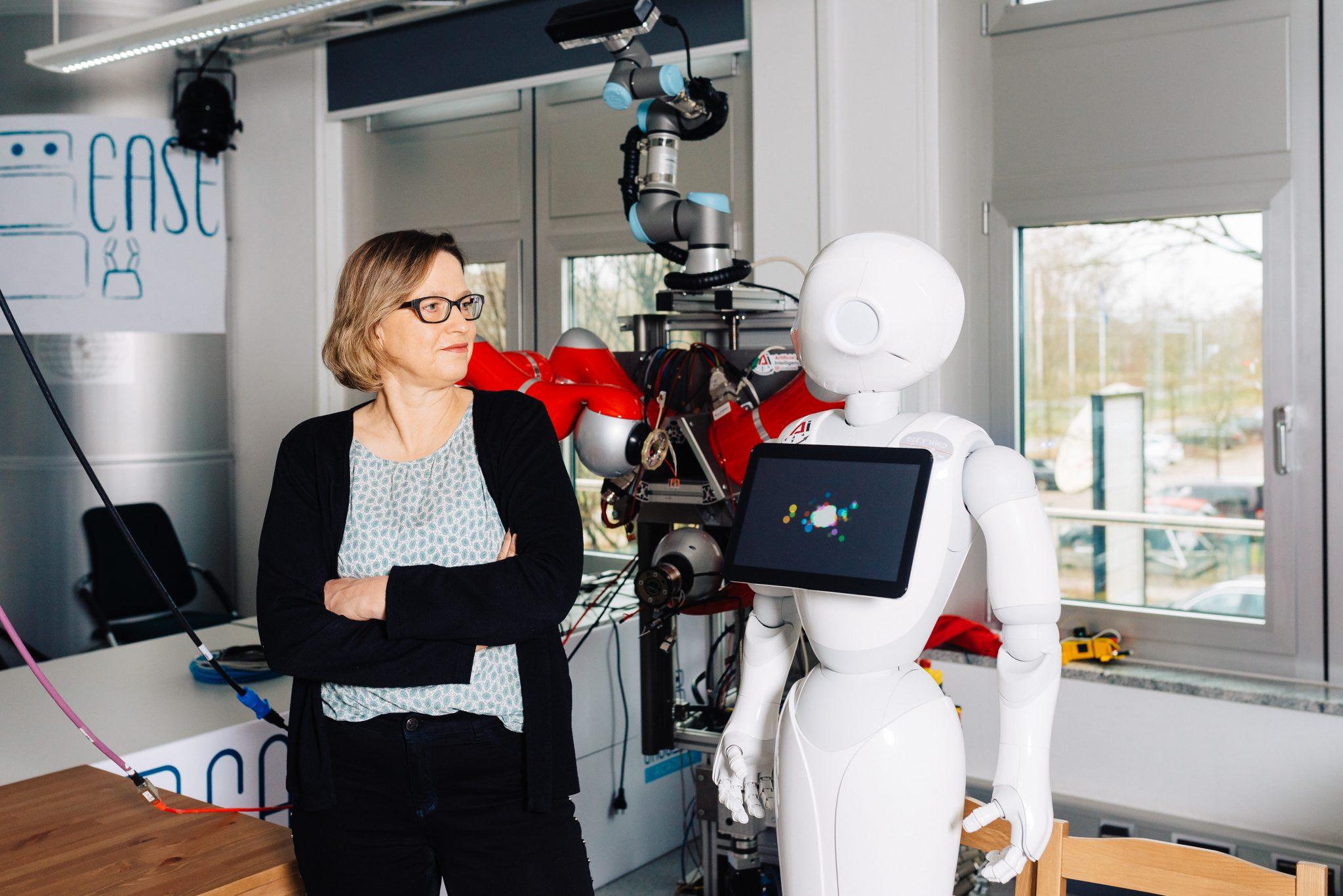 Die Projektleiterin und Zentrumsmanagerin des Bremer KI-Transfer-Zentrums, Inis Ehrlich steht neben dem humanoiden Roboter Pepper