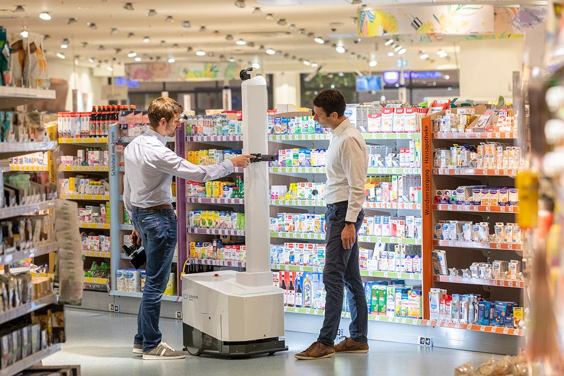 Die Geschäftsführer von Ubica Robotics Georg Bartels (l.) und Jonas Reiling führen in einer Filiale einer Drogeriekette in Bremen ihren Scanroboter vor.