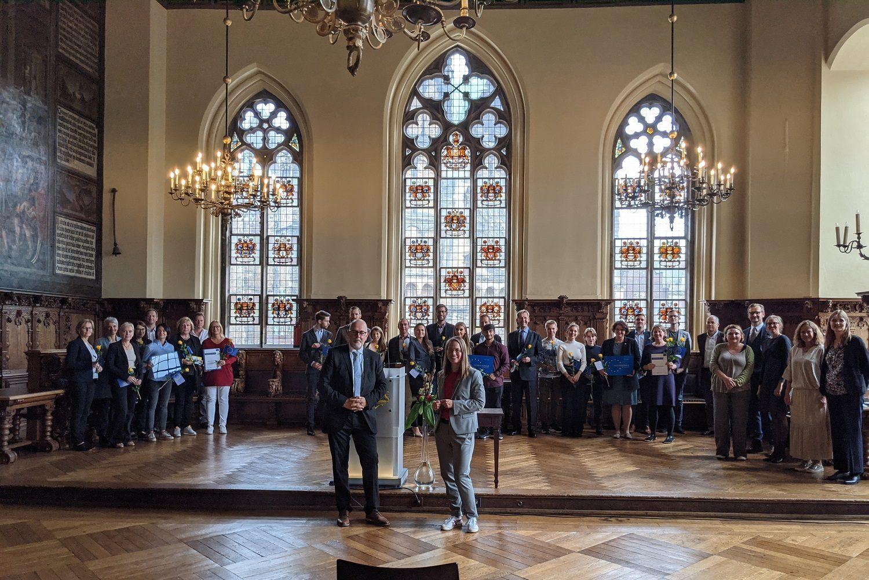 Menschen in einem Saal mit Buntglasfenstern im Hintergrund. Einige Menschen halten Zertifikate in den Händen